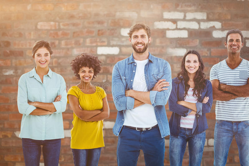 Composite image of group portrait of happy young colleagues. Group portrait of happy young colleagues against brick wall royalty free stock photos