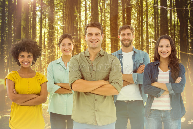 Composite image of group portrait of happy young colleagues. Group portrait of happy young colleagues against trees in a woods stock photo