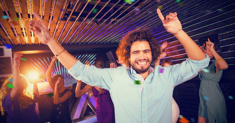 Composite image of group of smiling friends dancing on dance floor. Group of smiling friends dancing on dance floor against flying colours stock images