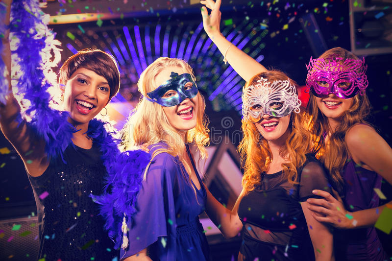 Composite image of group of smiling friends dancing on dance floor. Group of smiling friends dancing on dance floor against flying colours stock photos