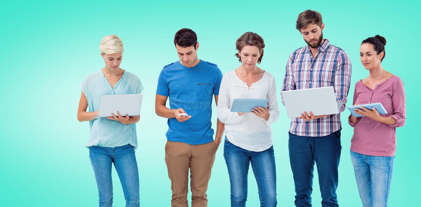 Composite image of group of young colleagues using laptop and tablet. Group of young colleagues using laptop and tablet against blue vignette background stock photos