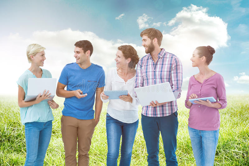 Composite image of group of young colleagues using laptop and tablet. Group of young colleagues using laptop and tablet against sunny landscape stock images