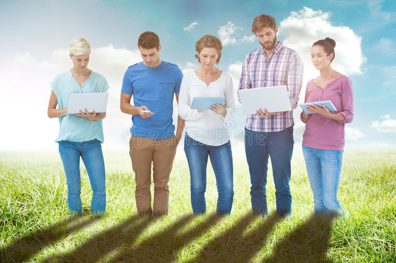 Composite image of group of young colleagues using laptop and tablet. Group of young colleagues using laptop and tablet against sunny landscape stock photography