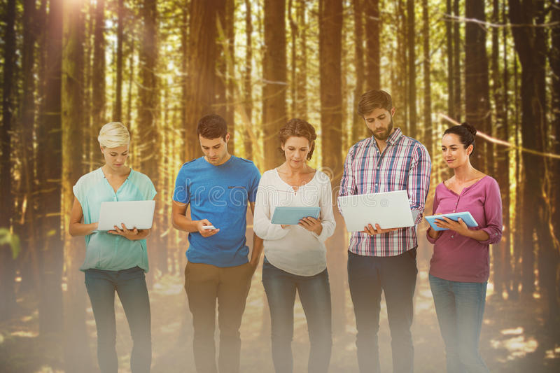 Composite image of group of young colleagues using laptop and tablet. Group of young colleagues using laptop and tablet against trees in a woods royalty free stock images