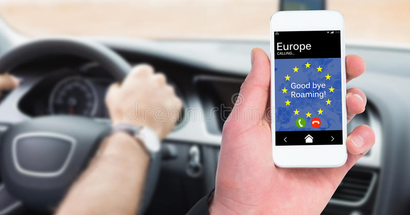 Composite image of hand of businessman holding smart phones. Hand of businessman holding smart phones against man driving with satellite navigation system royalty free stock photography