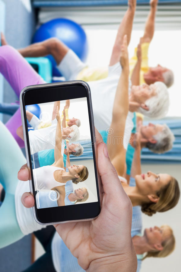 Composite image of hand holding mobile phone against white background. Hand holding mobile phone against white background against instructor performing yoga with stock photo