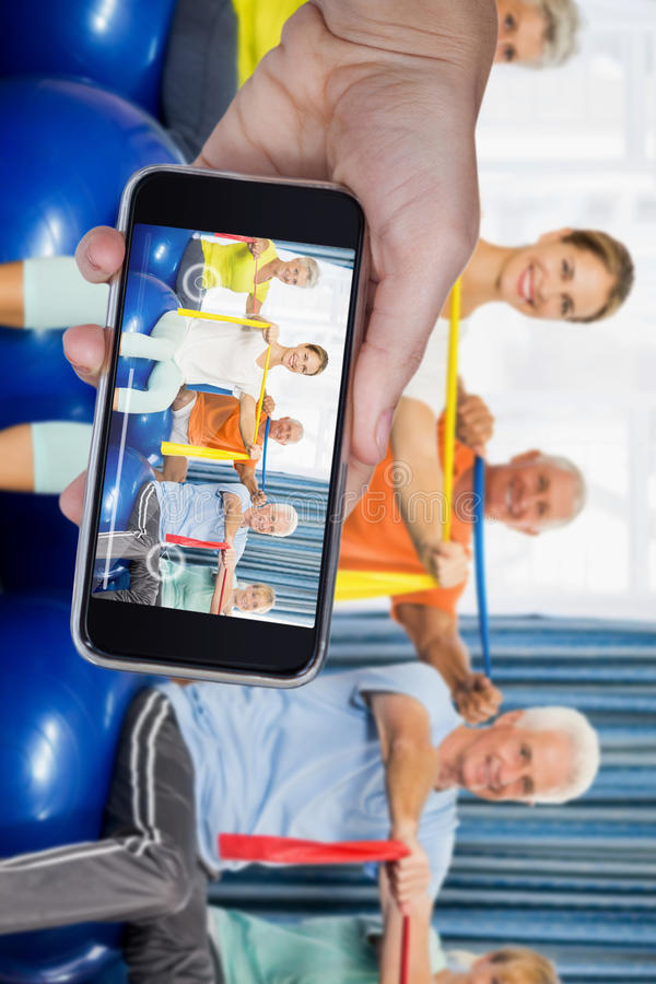 Composite image of hand holding mobile phone against white background. Hand holding mobile phone against white background against portrait of seniors using stock photos