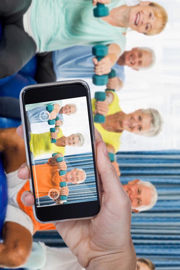 Composite image of hand holding mobile phone against white background. Hand holding mobile phone against white background against portrait of seniors using royalty free stock photos