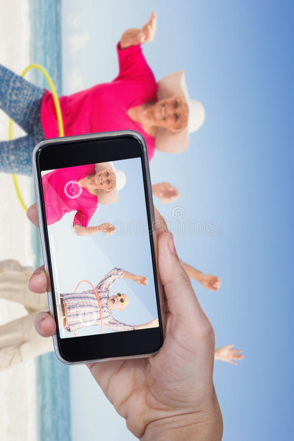 Composite image of hand holding mobile phone against white background. Hand holding mobile phone against white background against senior couple doing hula hoop stock image