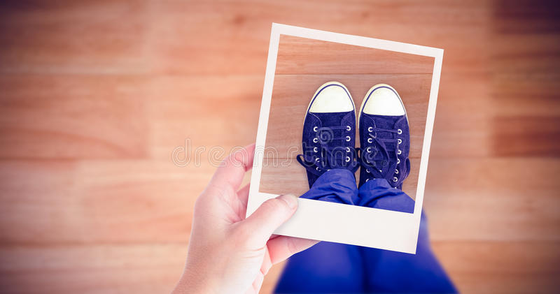 Composite image of hand holding polaroid picture. Hand holding Polaroid picture against wooden flooring royalty free stock photography