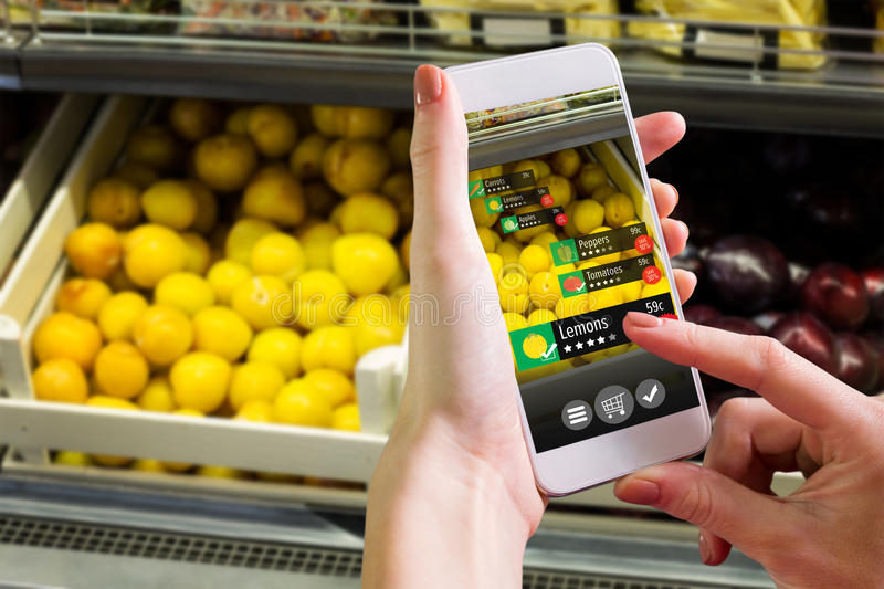 Composite image of hand holding smartphone. Hand holding smartphone against vegetable shelf at the supermarket royalty free stock image