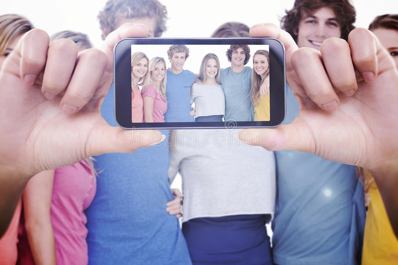 Composite image of hand holding smartphone showing. Hand holding smartphone showing against a group of friends smiling and holding each other royalty free stock images