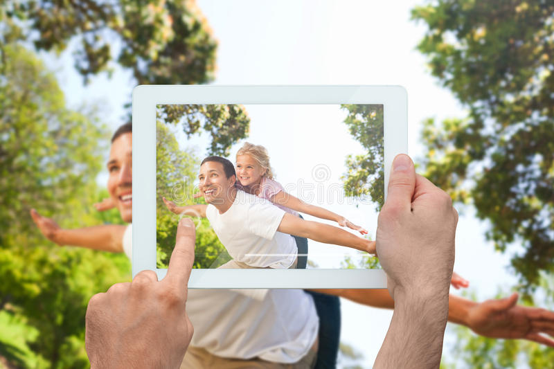 Composite image of hand holding tablet pc. Hand holding tablet pc showing father giving daughter a piggy back in park royalty free stock image
