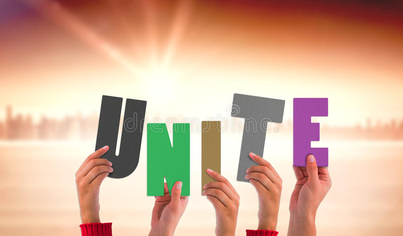 Composite image of hands holding up unite. Hands holding up unite against sun shining over city stock photos