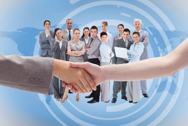 Composite image of handshake between two women. Handshake between two women against international business interface stock photo