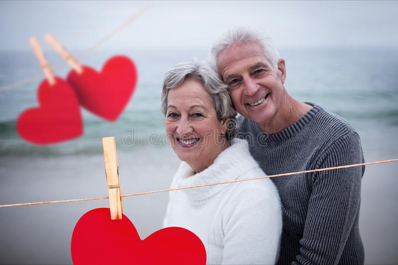 Composite image of hanging hearts and senior couple embracing on beach stock photography