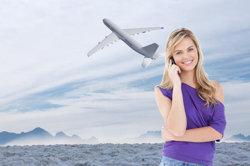 Composite image of happy blonde woman using her cellphone stock images