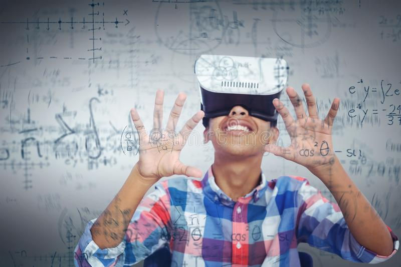 Composite image of happy boy looking through virtual reality simulator while sitting on chair royalty free stock photo