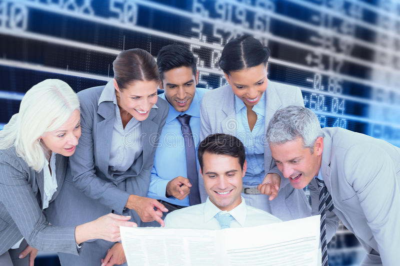 Composite image of happy business people looking at newspaper stock photo