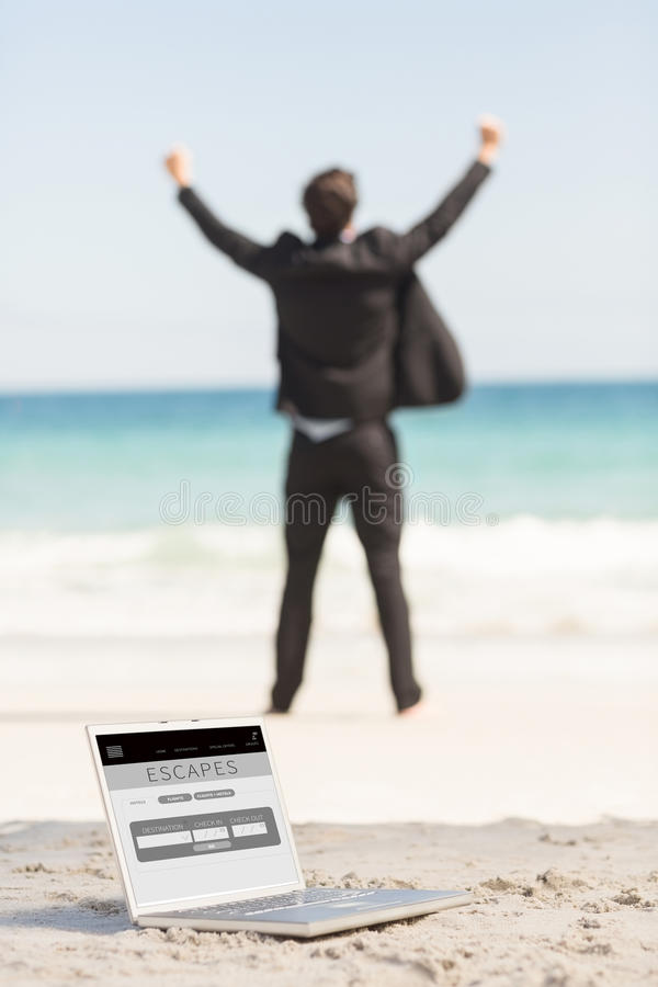 Composite image of happy businessman cheering in front of the sea stock photos