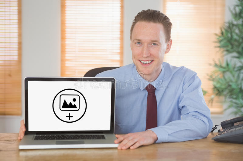 Composite image of happy businessman showing laptop screen. Happy businessman showing laptop screen against photography apps royalty free stock photography