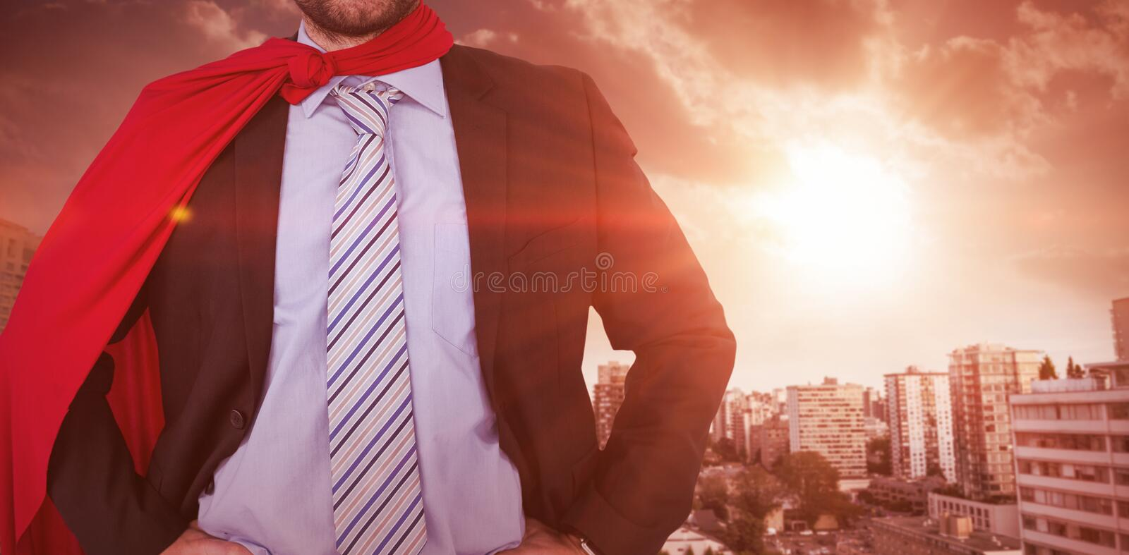 Composite image of happy businessman wearing cape and eye mask stock images