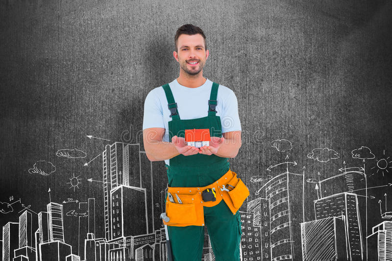 Composite image of happy construction worker holding house model. Happy construction worker holding house model against hand drawn city plan royalty free stock image