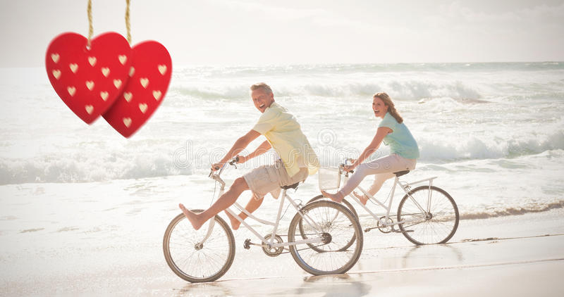 Composite image of happy couple on a bike ride. Happy couple on a bike ride against hearts hanging on a line royalty free stock photo