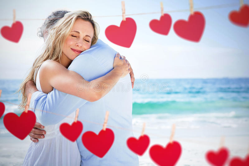 Composite image of happy couple hugging each other. Happy couple hugging each other against hearts hanging on a line stock photos