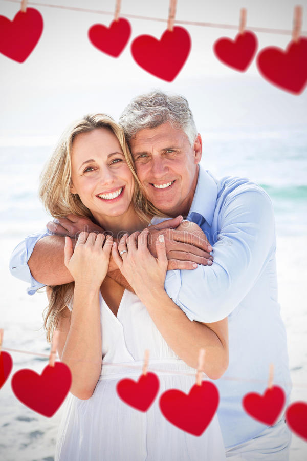 Composite image of happy couple hugging each other by the sea. Happy couple hugging each other by the sea against hearts hanging on a line royalty free stock photo
