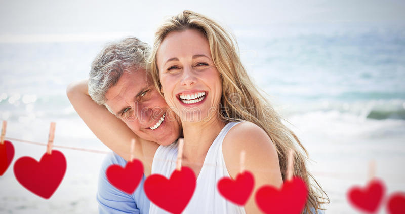 Composite image of happy couple laughing together. Happy couple laughing together against hearts hanging on a line royalty free stock photos