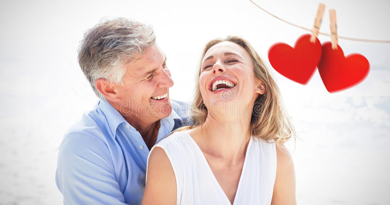 Composite image of happy couple laughing together. Happy couple laughing together against hearts hanging on line stock images