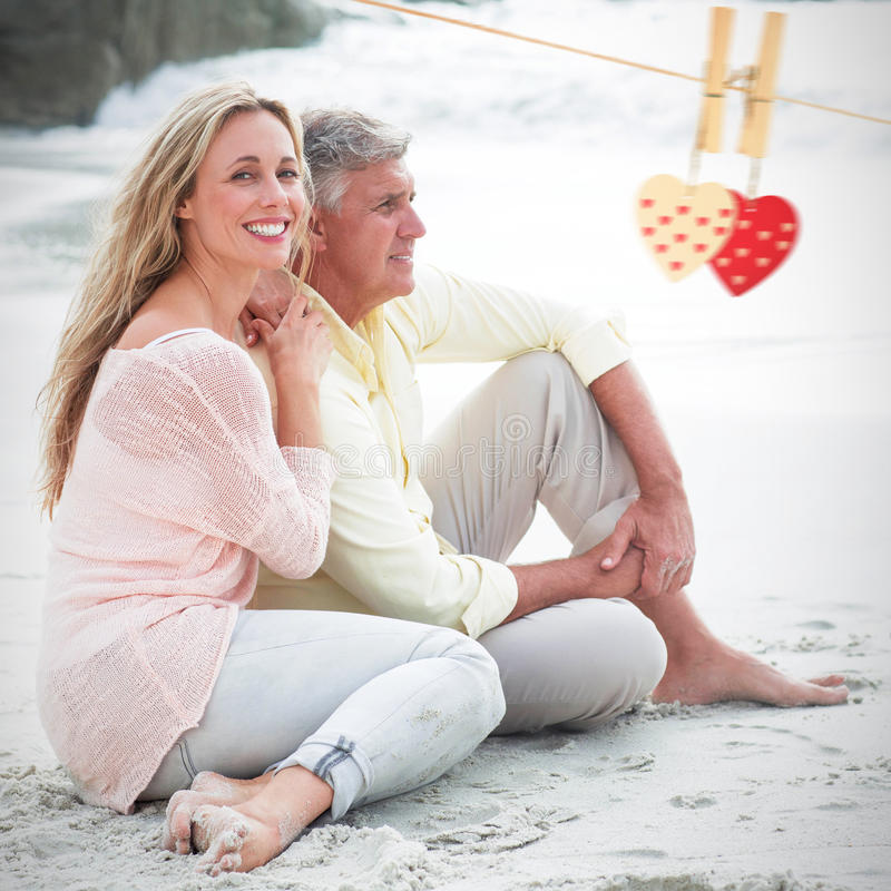 Composite image of happy couple sitting on the sand. Happy couple sitting on the sand against hearts hanging on a line stock photo