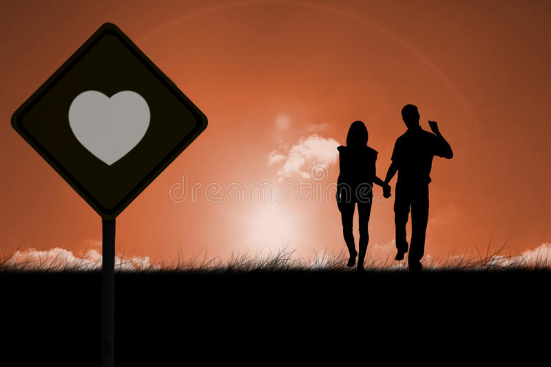 Composite image of happy couple walking holding hands. Happy couple walking holding hands against sun set stock image