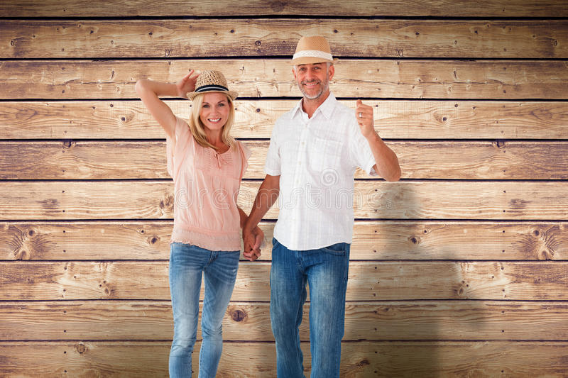 Composite image of happy couple walking holding hands. Happy couple walking holding hands against wooden planks background stock photography