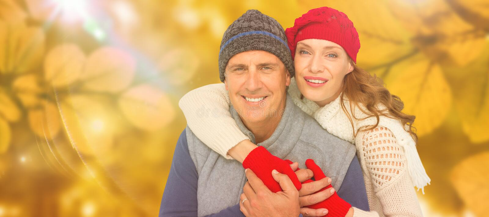 Composite image of happy couple in warm clothing. Happy couple in warm clothing against autumn scene stock image