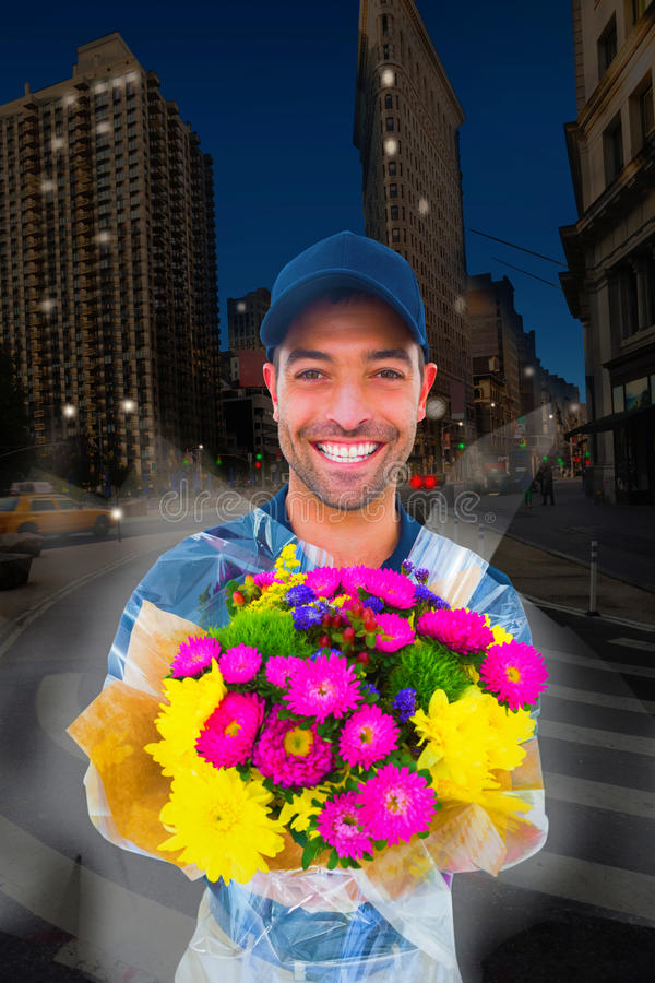 Composite image of happy delivery man holding bouquet royalty free stock photo