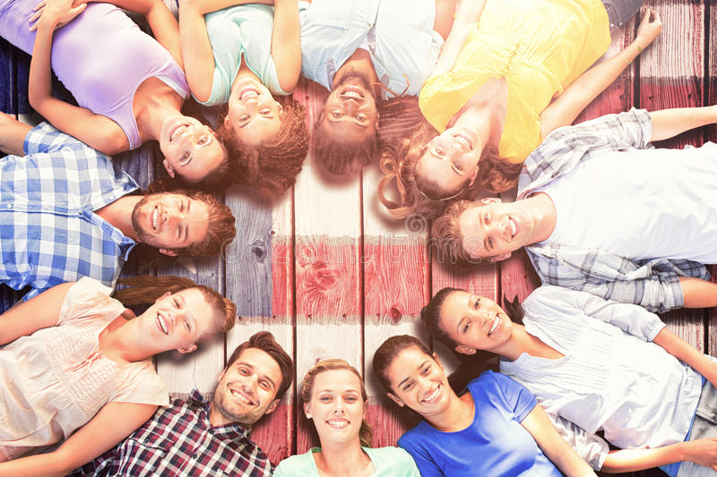 Composite image of happy friends lying in circle royalty free stock photography