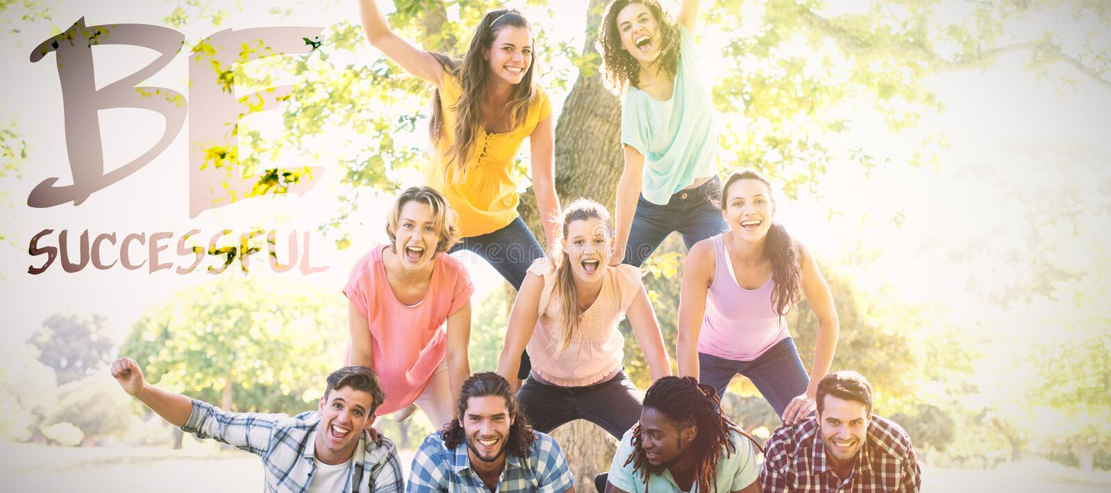 Composite image of happy friends in the park making human pyramid royalty free stock photography