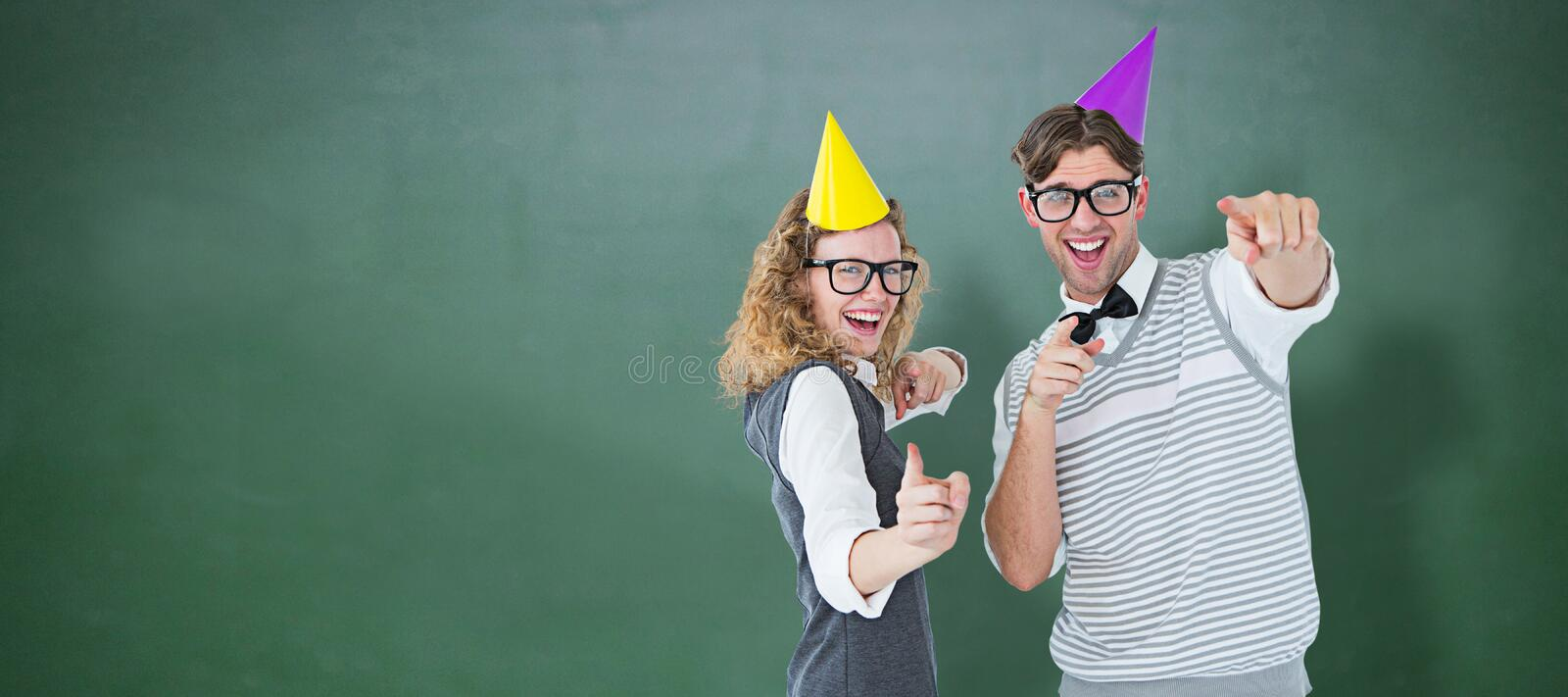 Composite image of happy geeky hispser couple dancing with party hat. Happy geeky hispser couple dancing with party hat against green chalkboard stock photography