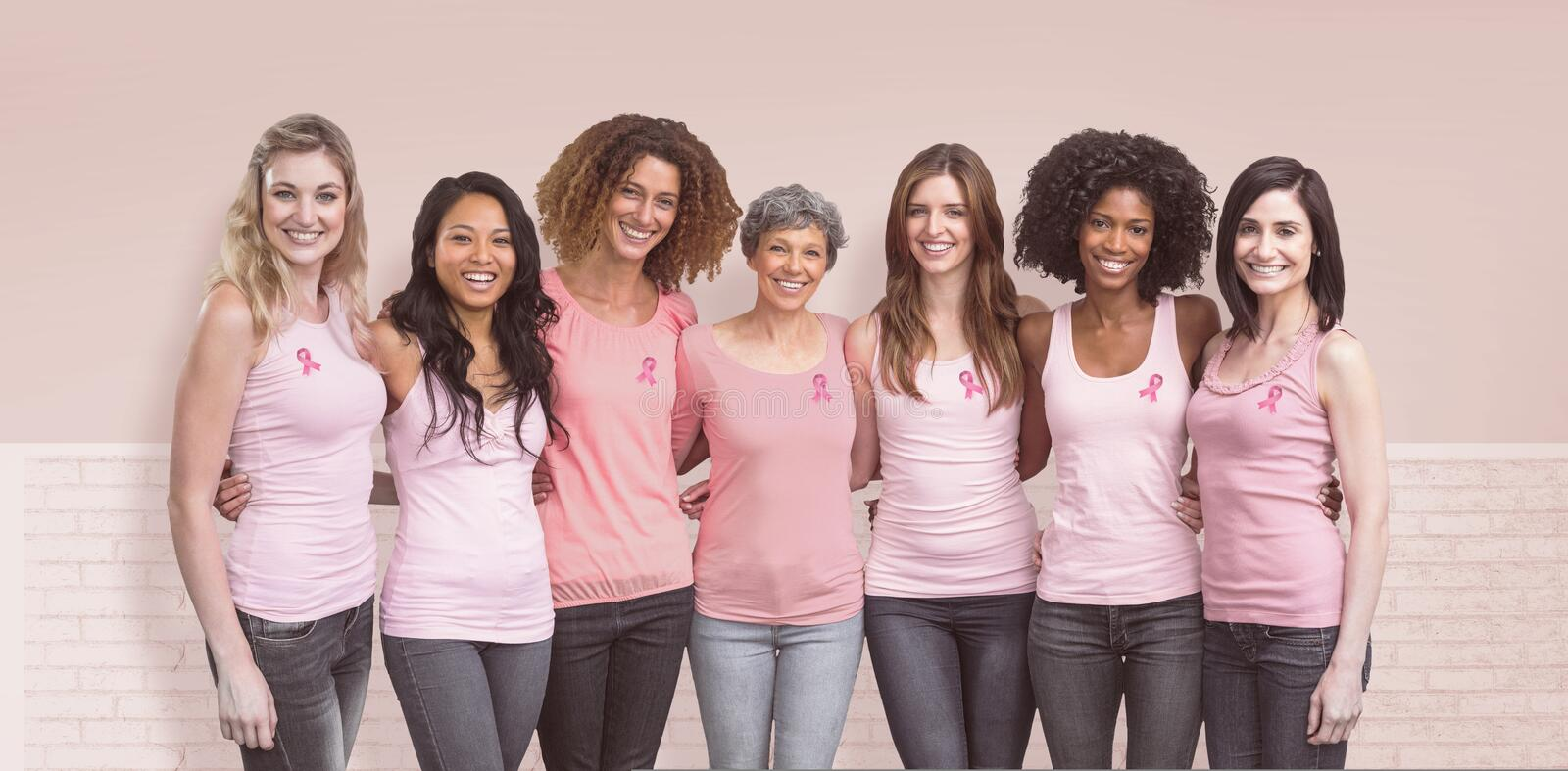 Composite image of happy multiethnic women standing together with arm around. Happy multiethnic women standing together with arm around against white wall stock photo