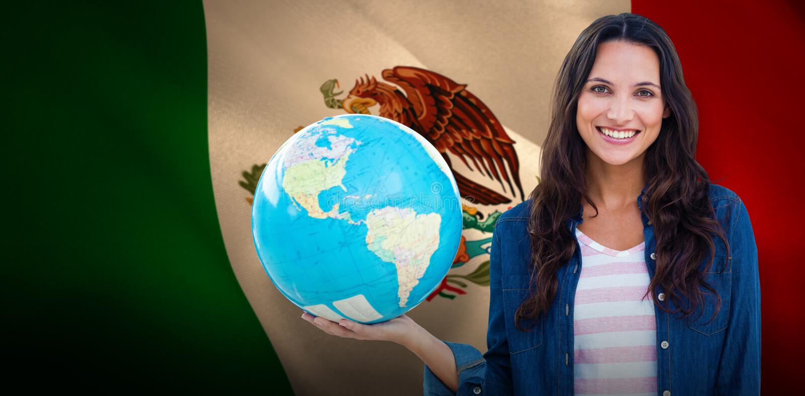 Composite image of happy woman with globe. Happy woman with globe against digitally generated mexican national flag stock photography