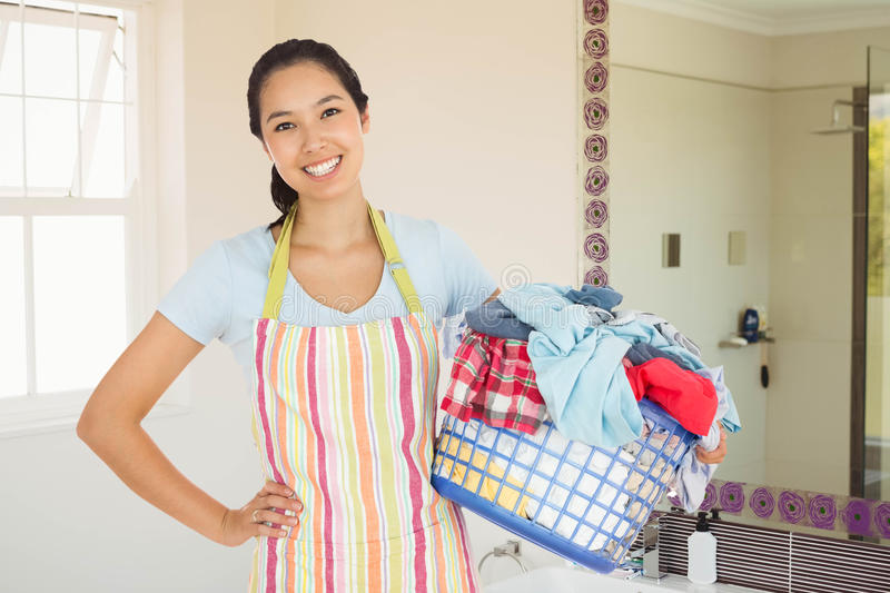 Composite image of happy woman with laundry basket stock photos