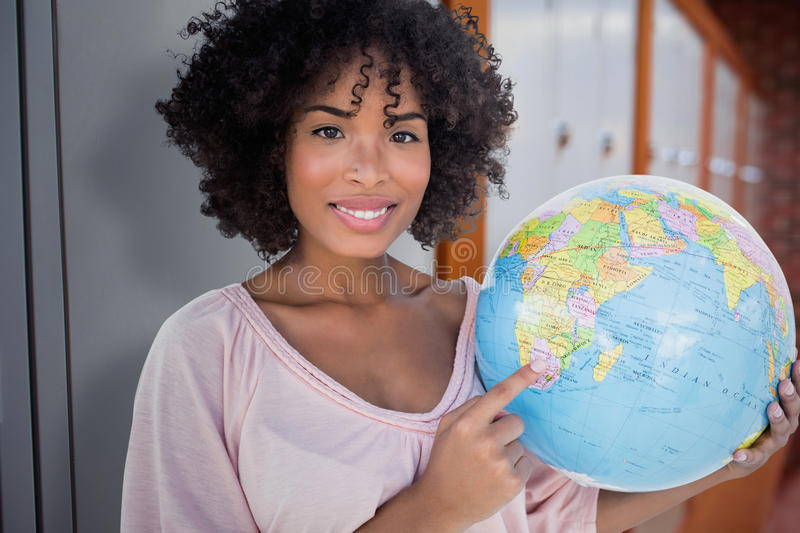 Composite image of happy woman pointing to globe royalty free stock photo