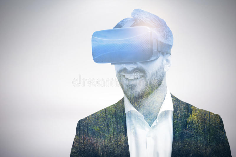 Composite image of happy young businessman using virtual reality glasses stock images