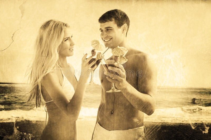 Composite image of happy young couple holding cocktails royalty free stock images