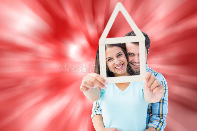 Composite image of happy young couple with house shape. Happy young couple with house shape against digitally generated twinkling light design royalty free stock photos