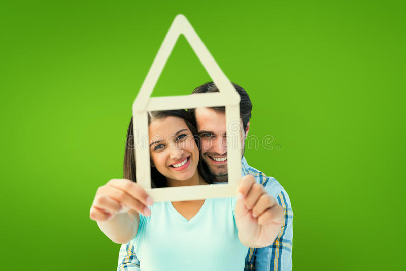 Composite image of happy young couple with house shape. Happy young couple with house shape against green vignette stock image