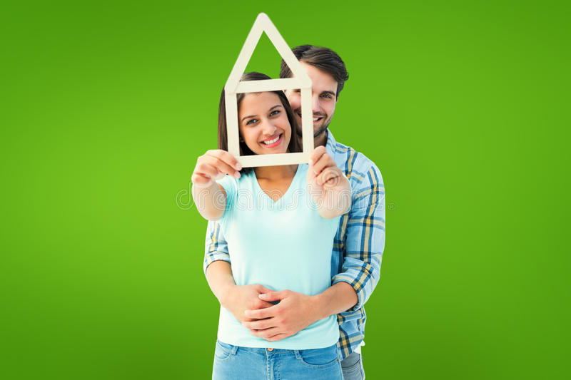 Composite image of happy young couple with house shape. Happy young couple with house shape against green vignette royalty free stock photography