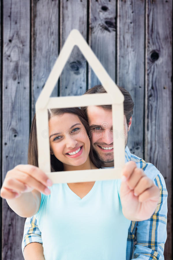 Composite image of happy young couple with house shape. Happy young couple with house shape against grey wooden planks royalty free stock photography